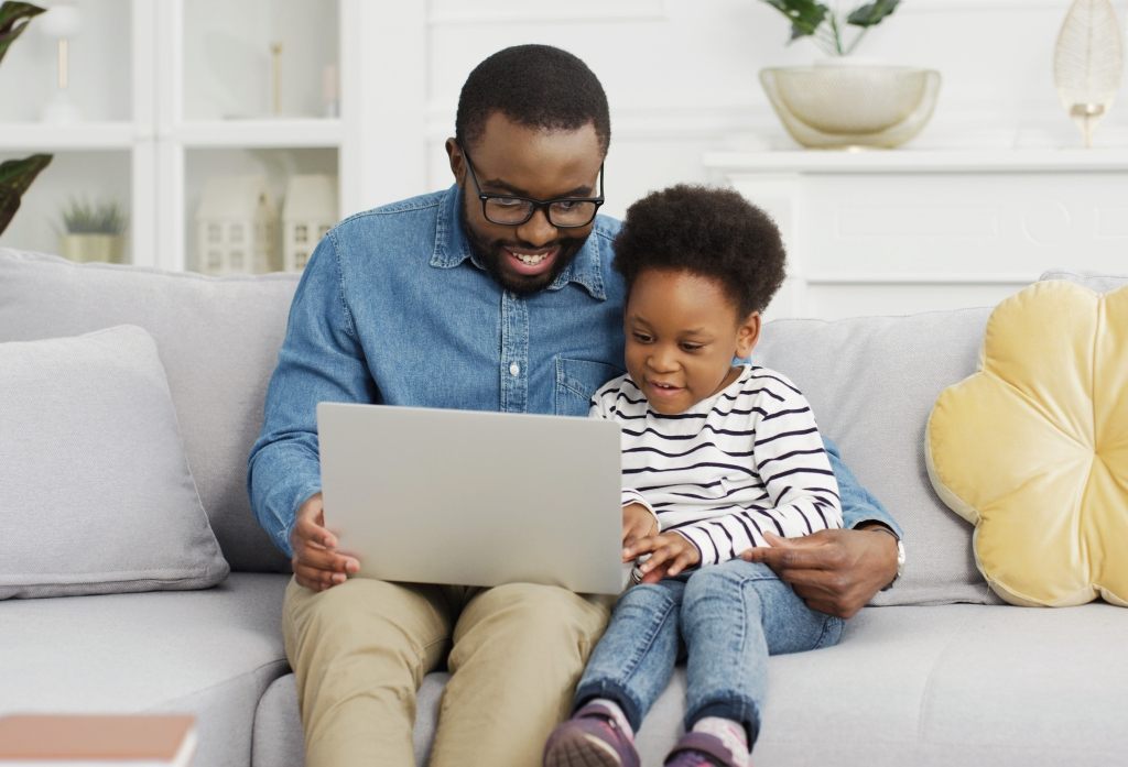Portrait of black father sitting with daughter on sofa using laptop.