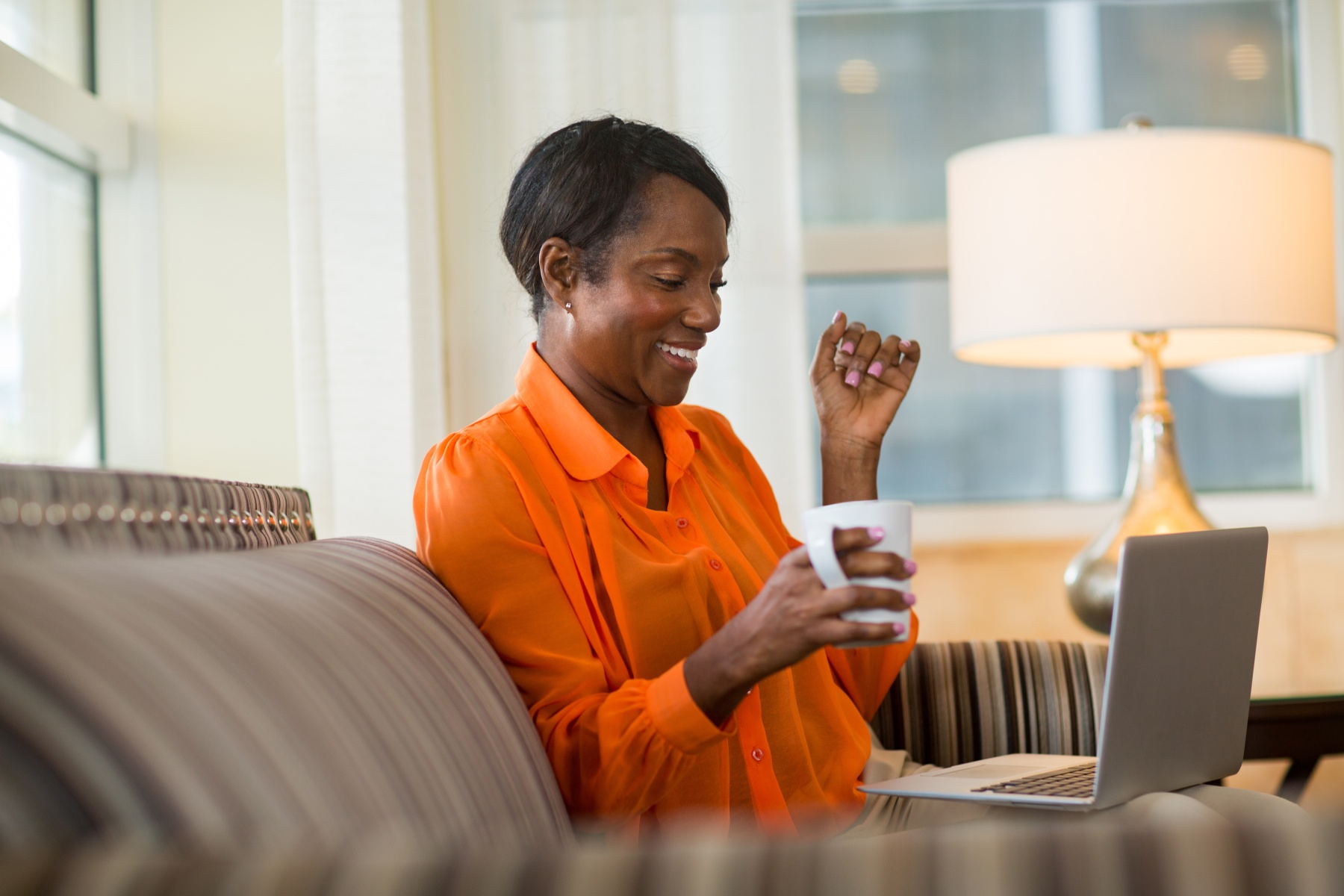 Smiling woman on her laptop working from home.