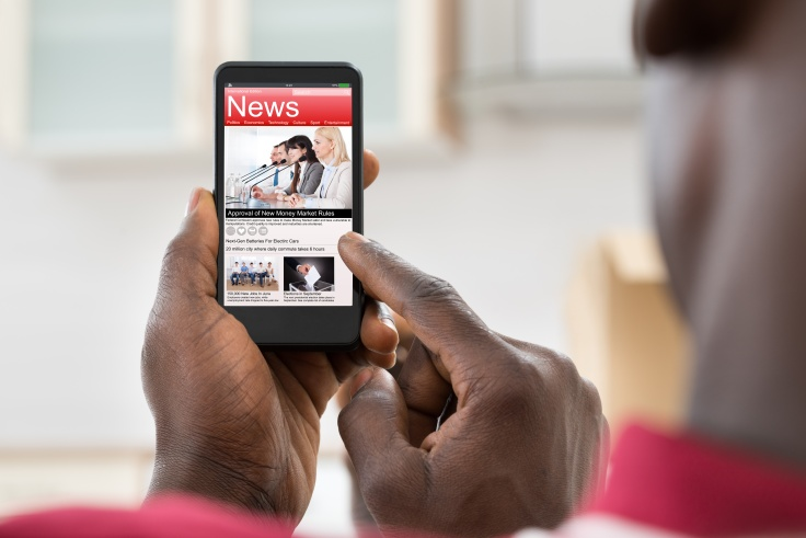 Over-the-shoulder close up of man reading news on mobile phone